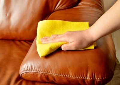 a woman cleaning a brown sofa at  home